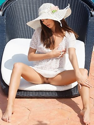 Michaela Isizzu is picture perfect in her floppy white hat and white lace cover-up .Relaxing poolside, Michaela teases her pussy while lounging in her