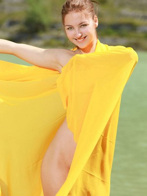 """""""A bright yellow cloth hugs Izabel A's naked body as she poses enthusiastically by the river."""""""